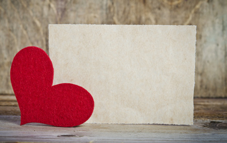 piece of paper: the form for a card on wooden background .   handmade heart from red felt is  in the left corner of the form Stock Photo