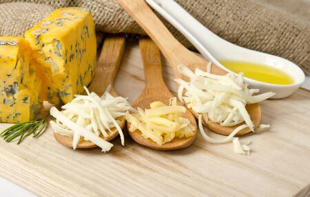 queso rayado: Queso rallado en cucharas de madera Foto de archivo