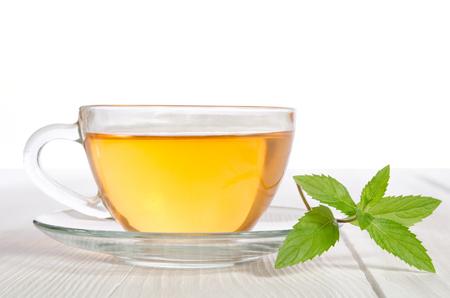 taza de t�: Taza de cristal de t� con menta en la mesa de madera blanca Foto de archivo