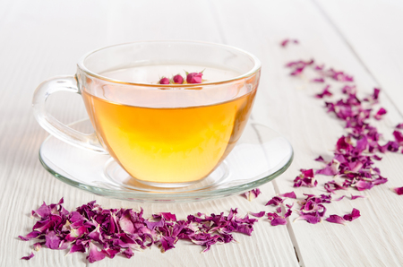 Rose tea and dried petals on white wooden table Reklamní fotografie - 49212231