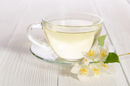 흰색 나무 배경에 자스민 차의 유리 컵