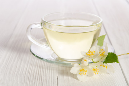 Glass cup of tea with jasmine on the white wooden background
