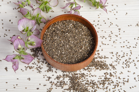 chia seed: Chia seed healthy super food with flower over white wood background. Salvia hispanica. Stock Photo