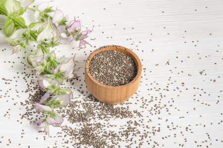 salvia hispanica: Chia seed healthy super food with flower over white wood background. Salvia hispanica. Stock Photo