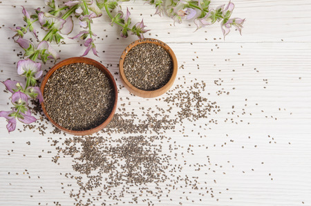 Chia seed healthy super food with flower over white wood background. Salvia hispanica. Standard-Bild