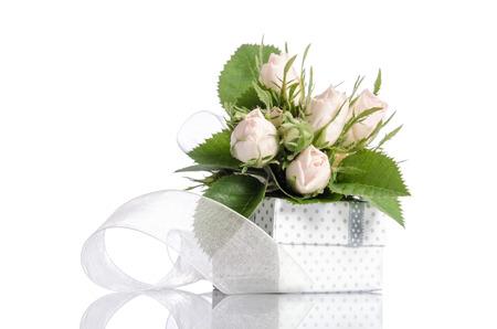 Blumenstrauß aus weißen Rosen und Geschenk-Box auf weißem Hintergrund