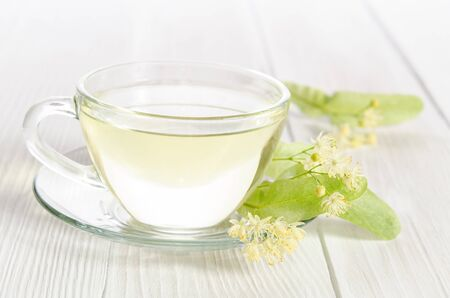 lime blossom: Glass cup of tea with linden on white  wooden table Stock Photo