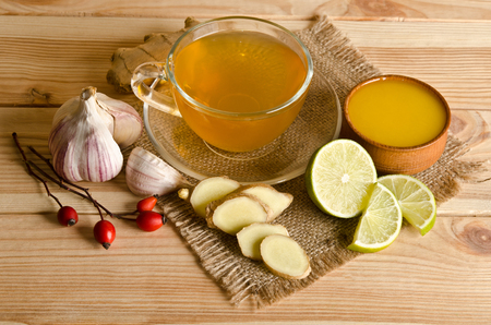 lemon: Cup of tea with lemon slices and ginger. Home antimicrobial therapy