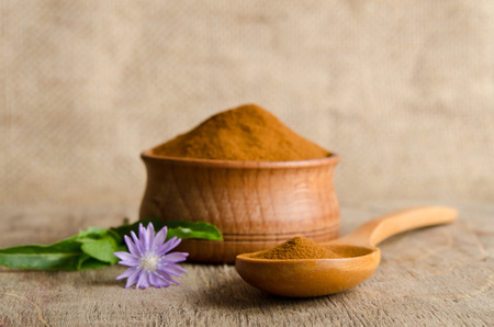 chicory coffee: Blue chicory flower and full wooden spoon of powder  instant chicory on old wooden table Stock Photo