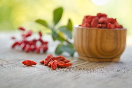 barberries: barberries and goji berries isolated on wooden table.