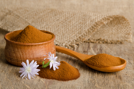 White chicory flower and full wooden spoon of powder  instant chicory on old wooden table Reklamní fotografie - 51056755