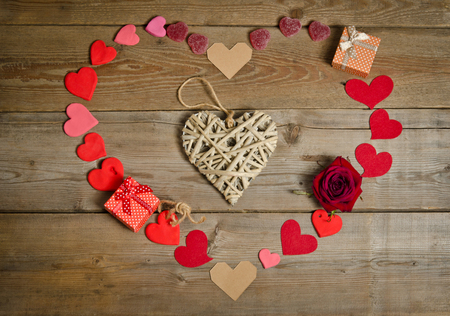 handmade: the handmade wicker heart in the centre and around many hearts handmade  in  shape of heart with two gift boxes  on the wooden board surface . Stock Photo