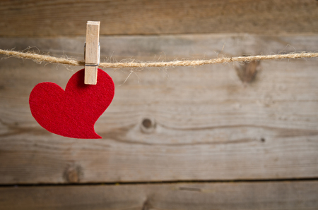 pack string: Red fabric heart  hanging on the clothesline. On old wood background.