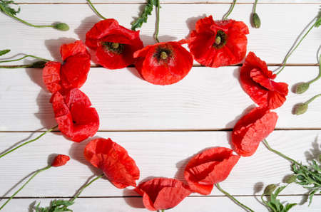 wooden insert: Beautiful red poppies in shape of heart on wooden background Stock Photo