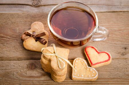 related: Cookies-hearts related together and a cup of tea on  wooden table