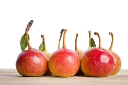 grouping: Small pears and leaves in a grouping on wooden table Stock Photo