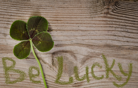 four fourleaf: four-leaf clover and text BE Lucky on wooden background