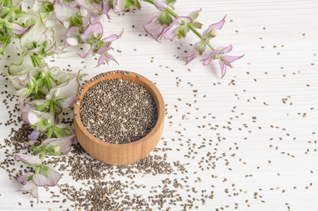 hispanica: Chia seed healthy super food with flower over white wood background. Salvia hispanica. Stock Photo