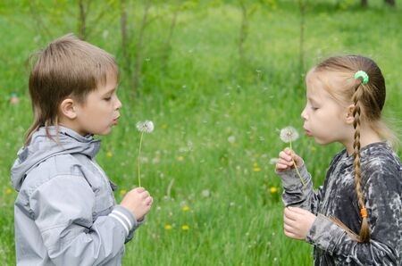 frendship: Boy and girl Standing In Field Blowing Dandelions