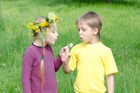 frendship: Boy and girl Standing In Field Blowing Dandelion
