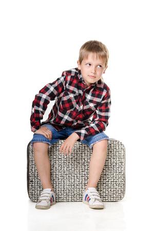 snění: boy sitting on suitcase isolated on white background