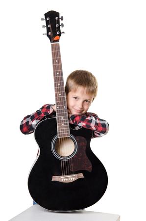 snění: chlapec sedí a drží kytaru ve svislé poloze izolovaných na bílém pozadí