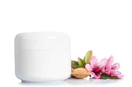 Jar of beauty cream isolated with flowers on white background