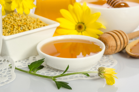 drizzler: The bowl of honey,  bowl with  pollen  and yellow flower isolated on white Stock Photo
