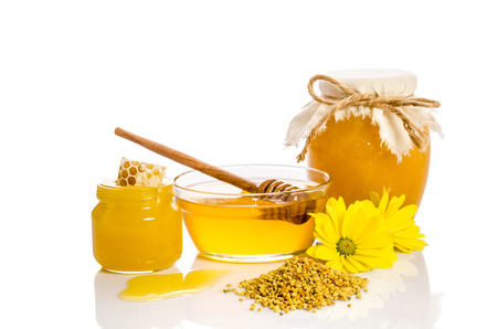 drizzler: The jars of honey, one of them with honeycombs, glass bowl with honey and wooden scoop with pollen isolated on white