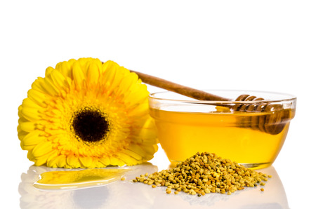 drizzler: a bowl of honey near a pile of pollen and flower isolated on white Stock Photo