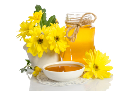 Yellow flowers, jar and bowl with honey isolated on white background Stock Photo