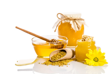 The bank of honey with honeycombs, glass bowl with honey and wooden scoop with pollen Stock Photo