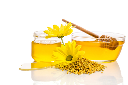 drizzler: the bowl and the jar of honey near a pile of pollen and flower isolated on white Stock Photo