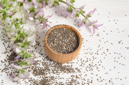 Chia seed healthy super food with flower over white wood background. Salvia hispanica. Stock Photo