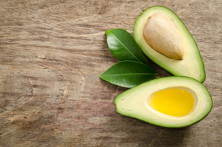 golden section: fresh avocado and half of avocado like a bowl for oil on wooden background.top view
