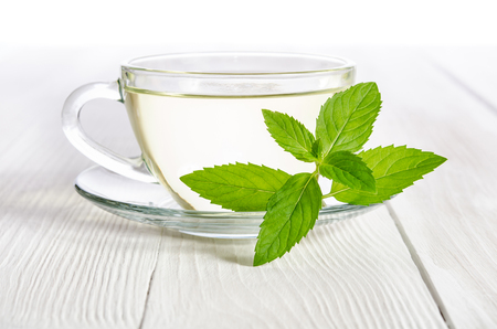 Glass cup of tea with mint on the white wooden table Stock Photo