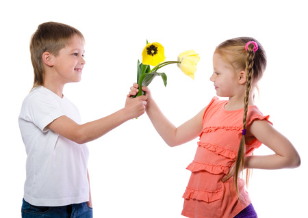 a boy gives a girl yellow tulips on white background