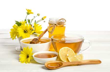 Yellow flowers, tea , lemon and honey on wooden table