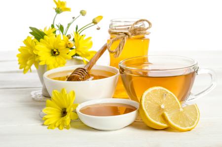 Yellow flowers, tea , lemon and honey on wooden table