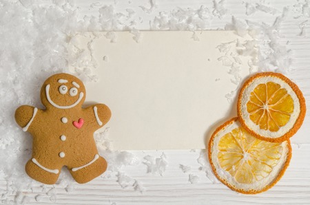 Christmas card with gingerbread and dried orange, snow over