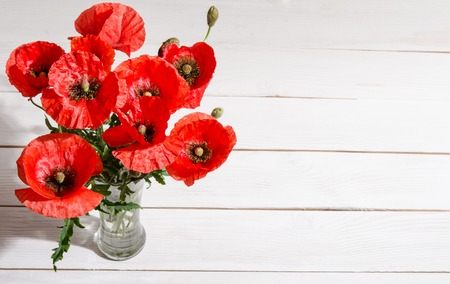 Bouquet of red poppies in glass vase on old white wooden table Stock Photo