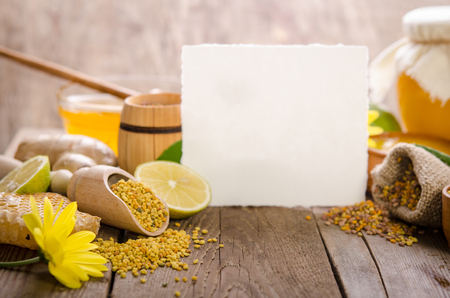 honeycombs ,honey, ginger, pollen, lemon on a wooden table with empty card for you text Stock Photo