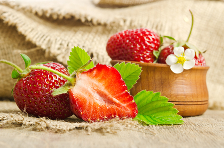 Ripe juicy strawberries on wooden table with burlap Reklamní fotografie