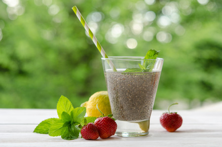 Chia seeds drink with water in transparent glass with lemon, mint and strawberry. outdoor photo. Stock Photo