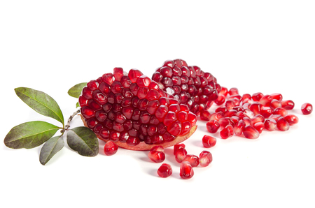 vitamin rich: Part of a pomegranate with pomegranate seeds and leaves isolated on white background Stock Photo