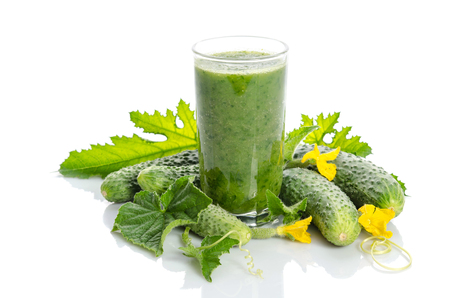 glass with green smoothie and  cucumbers, flowers, leaves isolated on white
