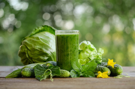 glass with green smoothie on a wooden table and  vegetables with mint leaves Stock Photo