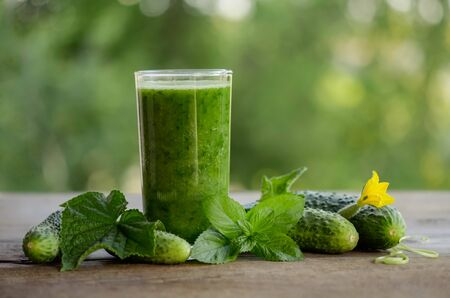 glass with green smoothie on a wooden table and  cucumbers with flowers and mint leaves
