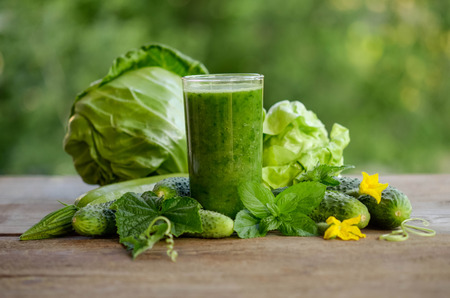 glass with green smoothie on a wooden table and  vegetables with mint leaves