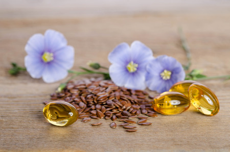 Flax seeds , beauty flowers and oil in caps on wooden background. Phytotherapy.